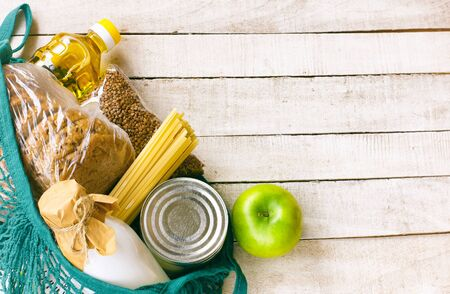 set of products, sunflower oil, milk, bread, canned food, pasta, apple, in mesh bag, donation and delivery concept Stock Photo