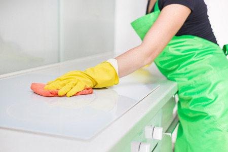 Closeup of female hands in rubber yellow gloves cleaning the cooker panel at home kitchen. Home, housekeeping concept. cleaning service