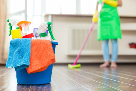 Cleaning service. Bucket with sponges, chemicals bottles and mopping stick. Rubber gloves and towel. Household equipment. woman with a mop