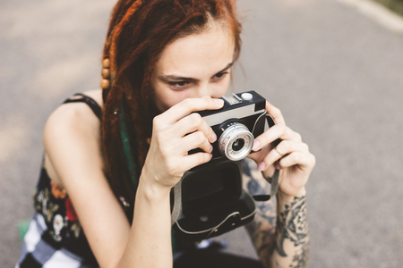 young girl with tattoos and dreadlocks photographs vintage camera in the park Banco de Imagens