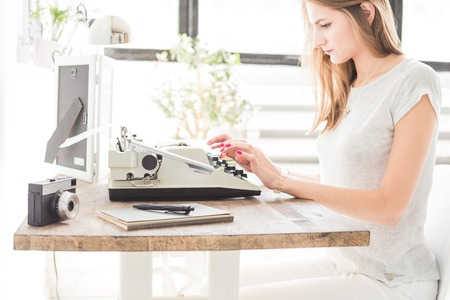 Young business woman working at home and typing on a typewriter. Creative Scandinavian style workspace