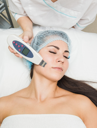 Beautician does the procedure of ultrasonic face cleaning for a young woman in a beauty salon
