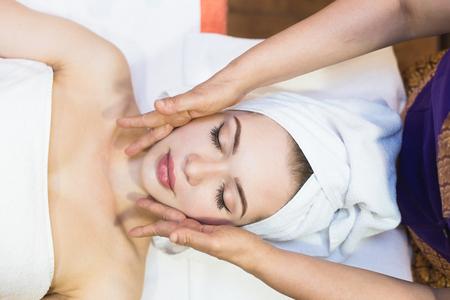beautiful girl enjoys face massage in spa salon. Procedures for beauty and rejuvenation. Thai massage Stock Photo
