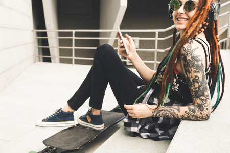 young girl with tattoo and dreadlocks listening to music while sitting on the steps