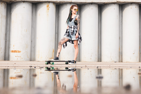 young girl with a longboard on the background of concrete structure