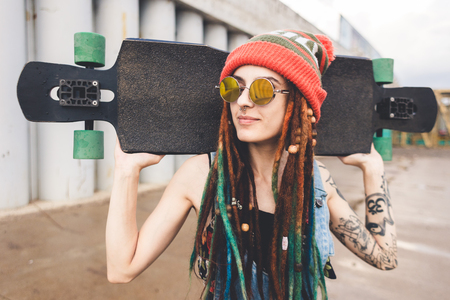 young girl in sun glasses and a cap stands with a longboard against the background of concrete structure