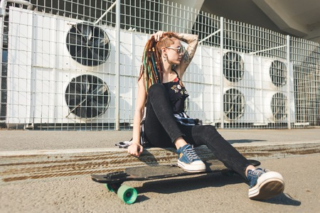 young girl with tattoo and dreadlocks on urban industrial background