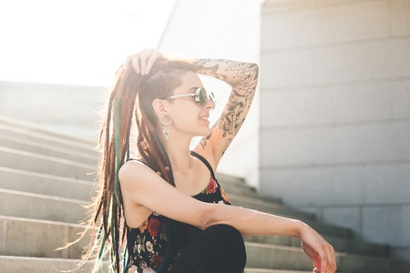 young girl with tattoo and dreadlocks sitting on the steps