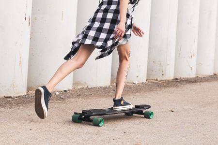 young girl with tattoo rides on a longboard
