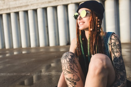 young girl with tattoos and dreadlocks in a blue cap sits on a longboard against the background of concrete structure