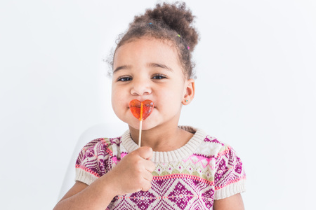 Portrait of a little girl in a colorful dress with a lollipop on a white background