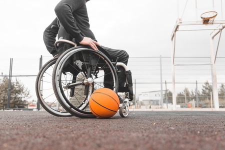 Young man in a wheelchair playing basketball. Stock Photo