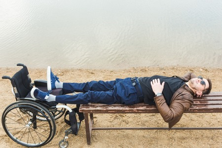 Young man resting, lying on a bench with legs on a wheelchair.