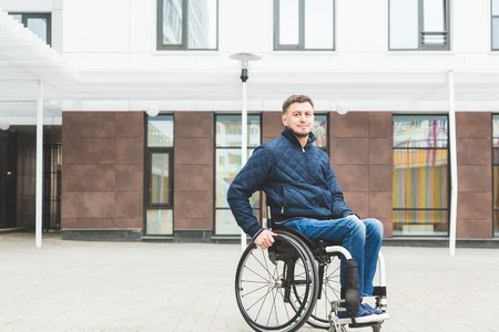 Young man in a wheelchair against the backdrop of a modern high-rise building. Stock Photo