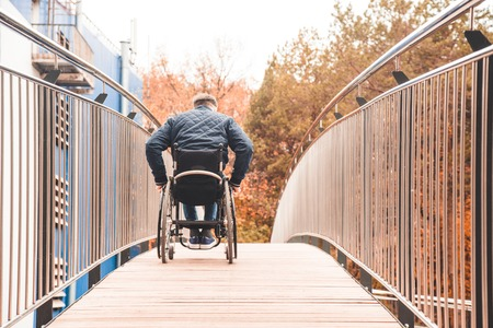 Man in a wheelchair use a wheelchair ramp. Banque d'images