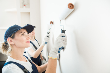 two beautiful women professionally paint the walls of the room. people in uniform, in overalls and a cap with a roller and brush, apartment renovation, interior design, tinting. isolated Stockfoto