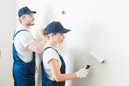 two worker professionally paint the walls of the room. people in uniform, in overalls and a cap with a roller and brush, apartment renovation, interior design, tinting. isolated Banque d'images - 113628770