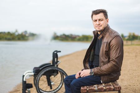 A young man sits on a bench by the lake, next to his wheelchair.