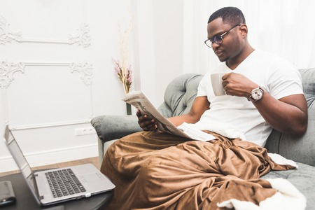 Young African American businessman remotely working at home on a laptop. Banco de Imagens