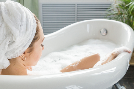 A young attractive girl relaxes in the bathroom and rests against the backdrop of a beautiful light interior. Spa treatments for beauty and health with skin care