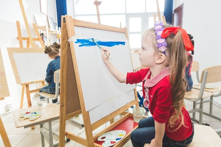 A group of preschool students and young teacher in drawing class paint in gouache. mixed race schoolgirl afroamerican and boy. Artwork