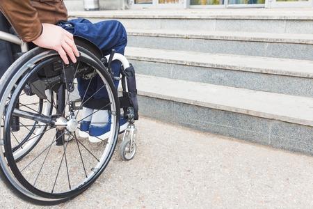 Hombre en silla de ruedas delante de escaleras.