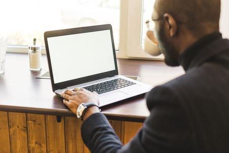 Joven apuesto hombre de negocios de piel oscura en un café trabajando detrás de una computadora portátil con una taza de té.