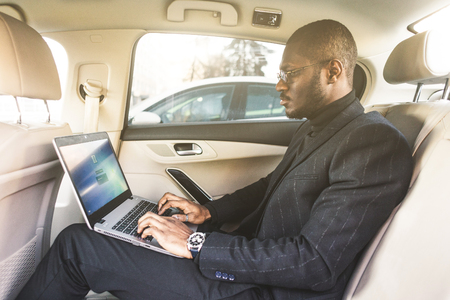 Man in a business suit write on laptop in the salon of an expensive car with leather interior.