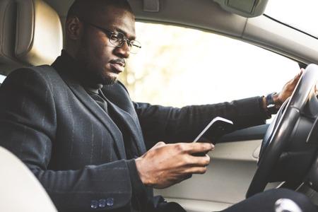 Een zakenman die een dure auto bestuurt, houdt een mobiele telefoon in zijn hand. Haastig leven. Stockfoto