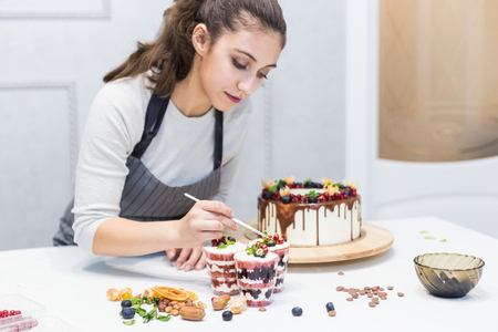 Decoration of the finished dessert. Pastry chef sprinkles confectionery with yellow powder. The concept of homemade pastry, cooking cakes. Banque d'images - 120260186