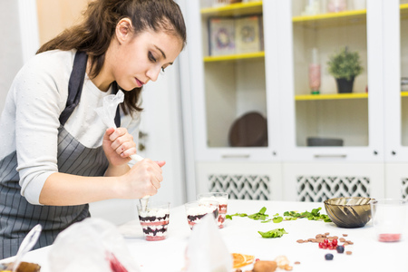 A confectioner prepares a trifle in three cups. Desserts are on the white table in the kitchen. The concept of homemade pastry, cooking cakes. Banque d'images - 120260401