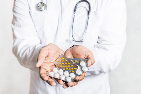 Handsome young doctor in a white coat with a stethoscope holds on the outstretched hand a pills in blisters.