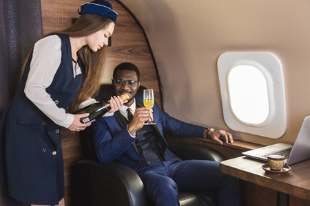 Young successful Afro-American businessman in glasses and a stewardess shows a bottle of wine in the cabin of a private jet. Service and flying first class. Фото со стока