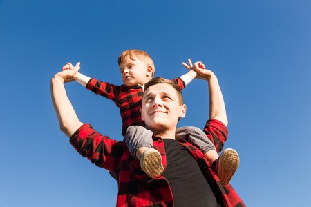 Young happy family with childrens having fun in nature. Little boy sitting on fathers shoulders