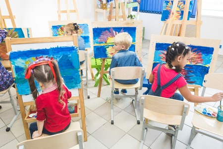 A group of preschool students and young teacher in drawing class paint in gouache. mixed race schoolgirl afroamerican and boy. Artwork, art class