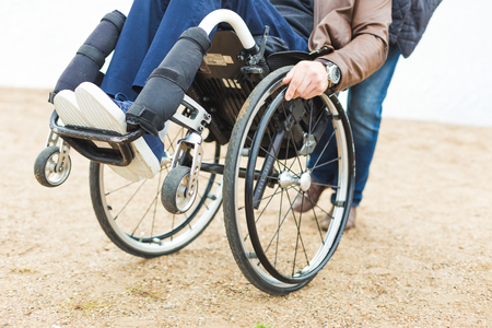 Young man in wheelchair with his assistant on a stroll through the park. Stock Photo