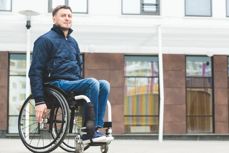 Young man in a wheelchair against the backdrop of a modern high-rise building.