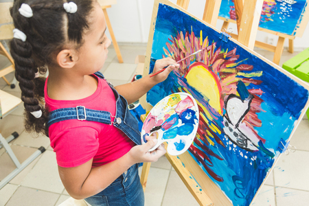 Mixed race little girl with a teacher in group of preschool student sat the drawing a picture. Painting on maelbert, palette and paints. Back to school and Education concept. Art class Banco de Imagens