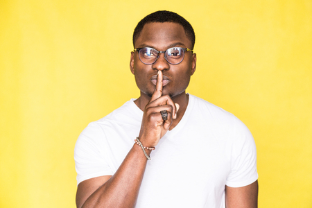 Portrait of a young handsome man in glasses showing a gesture of silence with a finger to his lips on a yellow background.