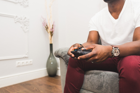 Young African American man playing a game console at home.