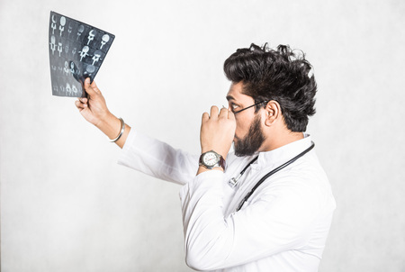 Handsome young doctor in a white coat with a stethoscope attentively checks the patients x-ray. Stock Photo