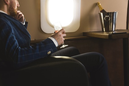 A young successful businessman in an expensive suit sits in the chair of a private jet with a glass of champagne in his hand and looks out the window Imagens