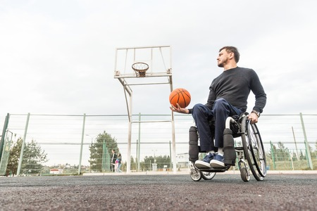 Young man in a wheelchair playing basketball. Banque d'images