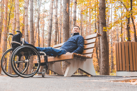 Young man resting sitting on a bench with his legs on his wheelchair.