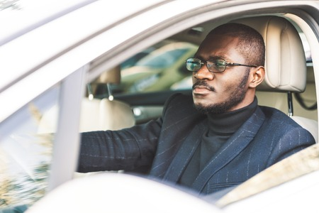 スーツを着た若いビジネスマンが高価な車の車輪に座っています。