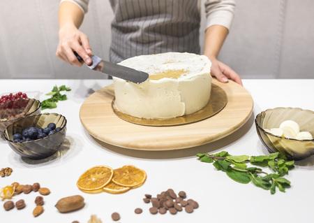 Konditor glättet weiße Sahne auf einem Kekskuchen mit einem Kochspatel. Das Konzept von hausgemachtem Gebäck, Kuchen kochen. Standard-Bild