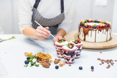 Dekoration des fertigen Desserts. Konditor besprüht Süßwaren mit gelbem Pulver. Das Konzept von hausgemachtem Gebäck, Kuchen kochen