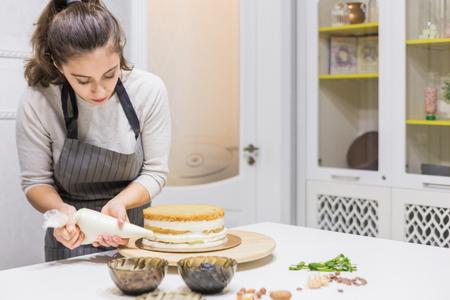 Pastelero con manga pastelera exprimiendo la crema sobre el pastel en la cocina. El concepto de repostería casera, tartas de cocina. Foto de archivo