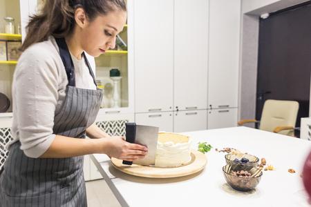El pastelero unta la crema blanca en un bizcocho con una espátula para cocinar. El concepto de repostería casera, tartas de cocina. Foto de archivo