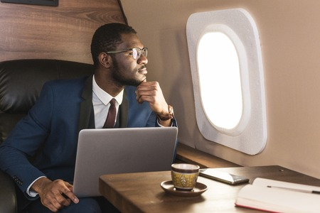 Attractive and successful African American businessman with glasses working on a laptop while sitting in the chair of his private jet. Stockfoto